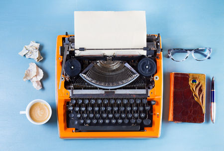 Workspace with orange vintage typewriter, coffee and notebook on blue background