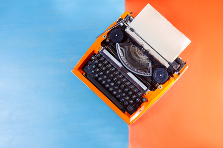 Workspace with orange vintage retro typewriter on blue and orange background