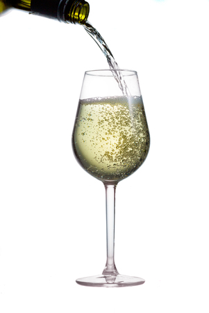 Pouring white wine from bottle to glass isolated on white background