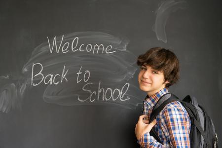 Tiener met rugzak en terug naar school die op zwarte raadsachtergrond wordt geschreven