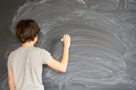 Teenager Boy with chalk in hand writting on empty black board