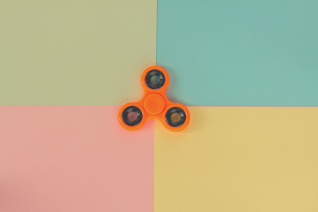 trendy fidget spinners - styled pop art flat lay scene with generic design orange spinner, retro toned