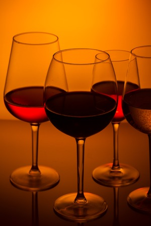 abstract liquor: Set of wine glasses with red, white and rose wine on orange background close up