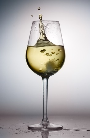 Hight glass of white wine with splash from ice