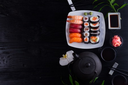 Japanese sushi dish with teapot and tea cups on black wooden background, top view