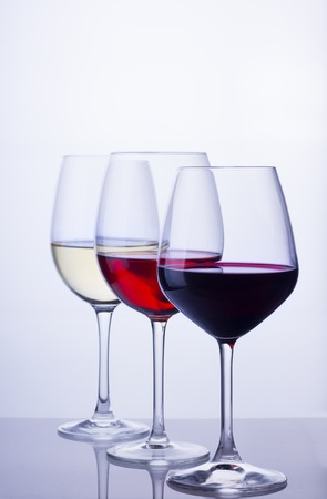 Row of three wine glasses with red, white and rose wine