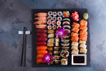 Japanese sushi big set with wooden black chopsticks on gray