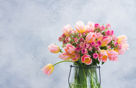 fresh pink and yellow tulips and roses in glass vase close up on gray background with copy space Stock Photo