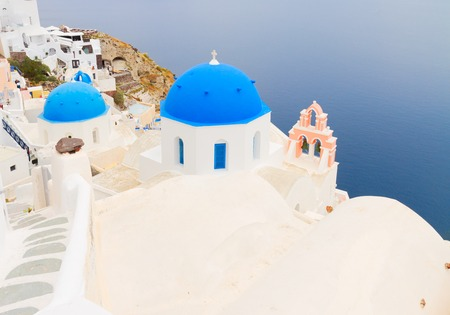 view of Aegan sea with blue church domes and towerbell, Oia, Santorini Stock Photo