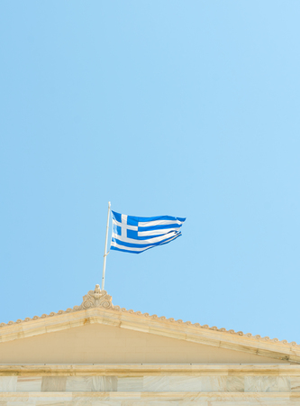 Flag of Greece on Athenian classical building in blue sky