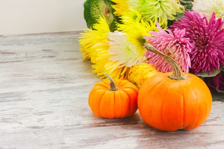 pile of raw orange pumpkins with fall flowers on white wooden table with copy space