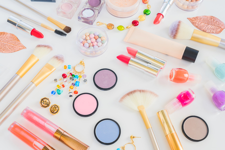 Colorful make up products flat lay scene on white background Imagens