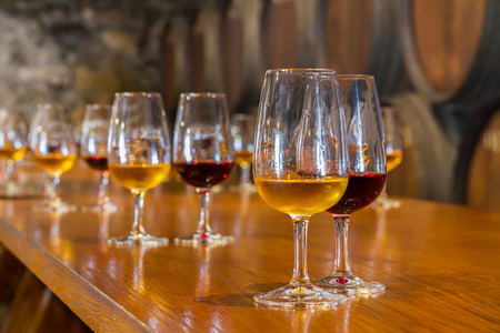 glasses of red and white port wine with barrels in background, wine degustation