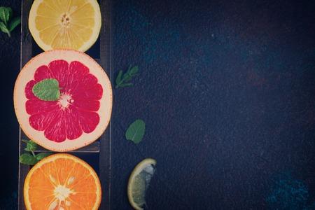 Orange, lemon and grapefruit with citrus reamer on dark background, retro background Stock Photo