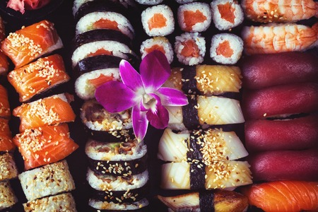 Japanese sushi big set with orchid flower, top view, retro toned