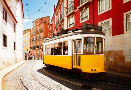 yellow tram on narrow street of Alfama district, Lisbon, Portugal, retro toned Stock fotó