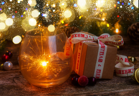 Christmas magic glowing light with gift box and evergreen twig on wooden background Stock Photo
