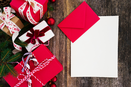 Christmas gift giving and shopping list concept - christmas presents in red paper boxes on wooden table, flat lay with copy space on empty paper note Stock Photo