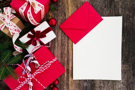 Weihnachtsgeschenk geben und Einkaufslistenkonzept - Weihnachtsgeschenke in den roten Papierkästen auf Holztisch, flache Lage mit Kopienraum auf leerer Papieranmerkung Standard-Bild