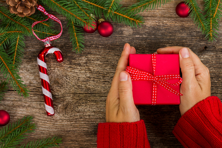 Christmas gift giving - someones hand in red knitted sweater holding red box with present Stock Photo