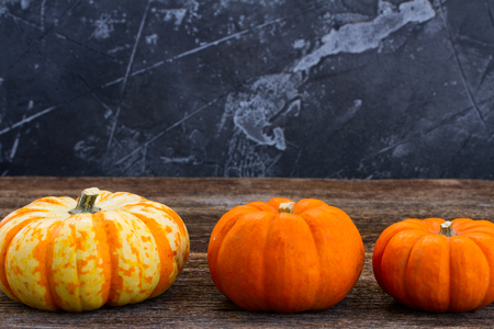 Row of fall harvest of pumpkins on wooden table Stock Photo
