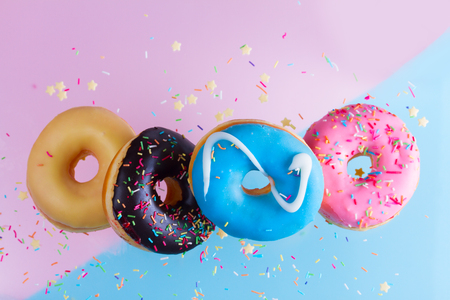 falling doughnuts border - mix of multicolored sweet donuts with sprinkles on blue and pink background