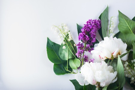 Floral flat lay scene of fresh flowers - lilac, peonies and lilly of the walley flowers on white background Stock Photo