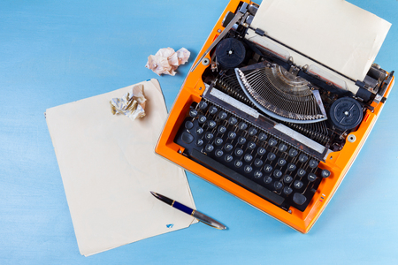 Workspace with orange vintage typewriter and empty paper on blue wooden background