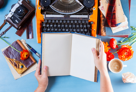 Workspace with orange retro typewriter, someones hands holding open book with copy space