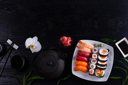 Japanese sushi dish with teapot and tea cups on black wooden background, top view flat lay border