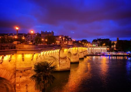 Pont Neuf and Cite island over Seine river at night, Paris, France, retro toned