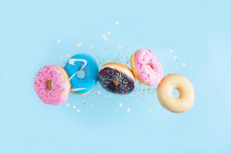 vliegende donuts - mix van veelkleurige zoete donuts met hagelslag op blauwe achtergrond
