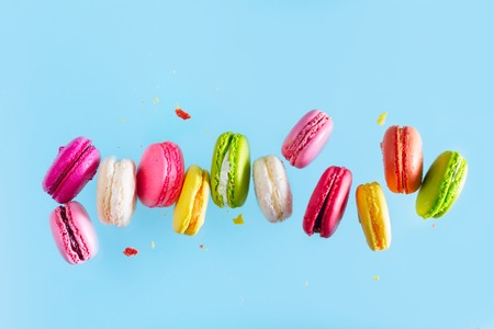 Assorted colorful macaroons falling cookies on blue background Banque d'images