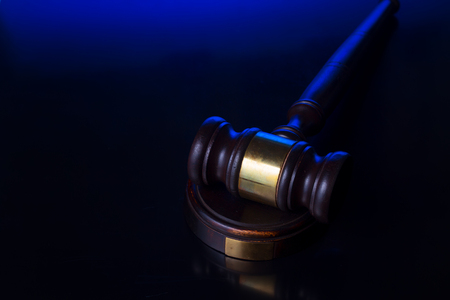 Law and justice concept - wooden law gavel pn blue and black background