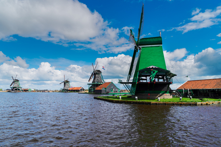 Dutch scenery with windmills over river, Zaanse Schans at summer day, Netherlands Stock Photo