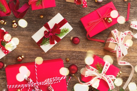 Christmas gift giving - pile of wrapped in red and white paper christmas gift boxes on wooden background with lights