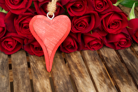 red fresh roses with red heart for Valenrines Day laying on aged wooden table Stock Photo