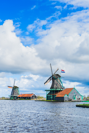 Dutch scenery with windmill of Zaanse Schans over river water at spring day, Netherlands Stock Photo
