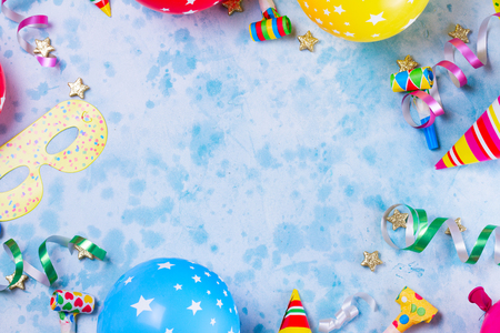 Bright colorful carnival or party scene frame of balloons, streamers and confetti on blue. Flat lay style, birthday or party greeting card with copy space.