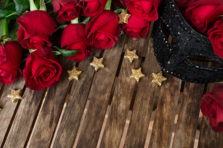red fresh roses with black lacy carnival mask, copy space on wooden table