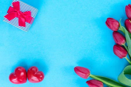 posy of red tulips with two hearts ans gift, copy space on blue background