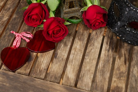 red fresh roses with mask and eiffel tower on wooden table, romantic date concept