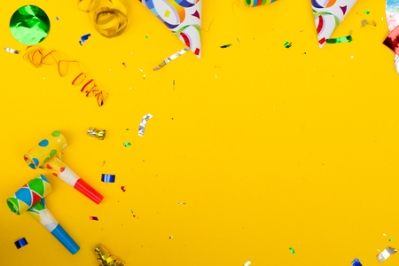 Bright colorful carnival or party scene border of confetti on yellow table. Flat lay birthday or party greeting card with copy space.
