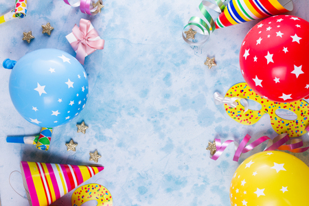 colorful carnival or party scene of balloons, streamers and confetti on blue table. Flat lay style, birthday or carnival party greeting card with copy space. Stock Photo