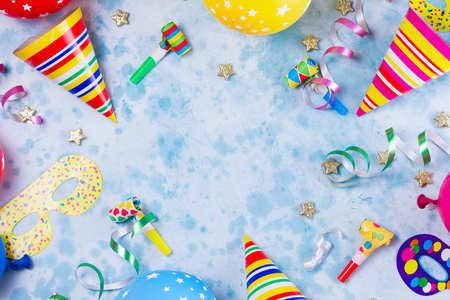 colorful carnival or party scene frame of balloons, streamers and confetti on blue table. Flat lay style, birthday or party greeting card with copy space. Stock Photo