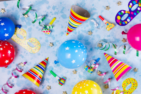 colorful carnival or party pattern of balloons, streamers and confetti on blue table. Flat lay style, birthday or party greeting card.