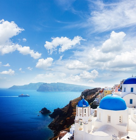 volcano caldera with blue church domes at sunny day with cloudy sky, Oia, Santorini