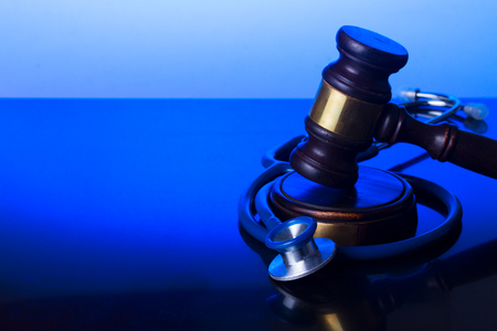 Wooden law gavel with stethoscope on blue - medical law and justice concept