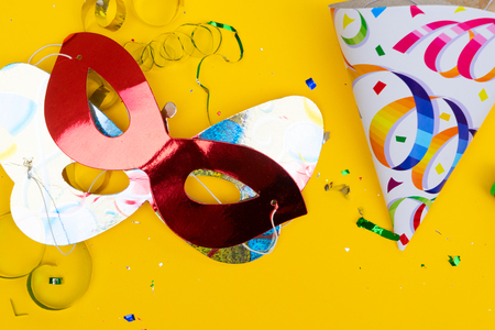 Bright colorful carnival or party scene of confetti and masks on yellow table. Flat lay, birthday or party scene. Stock Photo