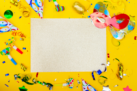 Bright colorful carnival or party scene of confetti and masks on yellow. Flat lay style, birthday or party scene with copy space on golden card